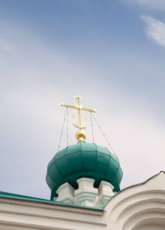 Glowing  ornamental church cross on a blue sky background    Stock Photo - 9926792