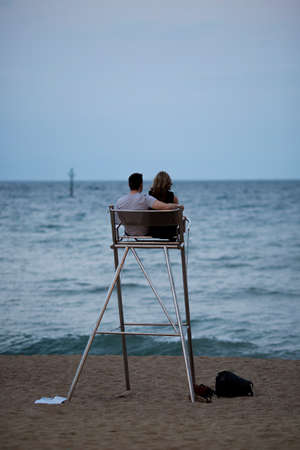 watchtower: Stock Photo - BARCELONA - JUL 09 Beach,  A young couple sitting on a watchtower at the beach and enjoying the evening while watching the see