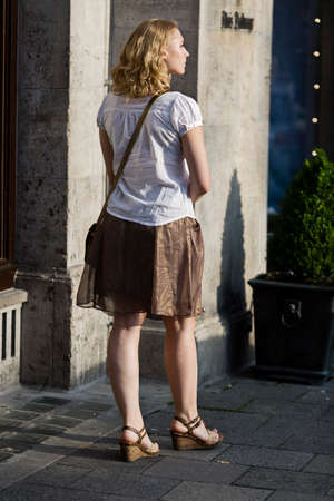 orte: Munich, Germany - July 15, 2014  Young woman with long blond hair is walking in front of Dalmayer  famouse German Cafee Shop  in Munich  It s afternoon a beautiful summer day   Editorial