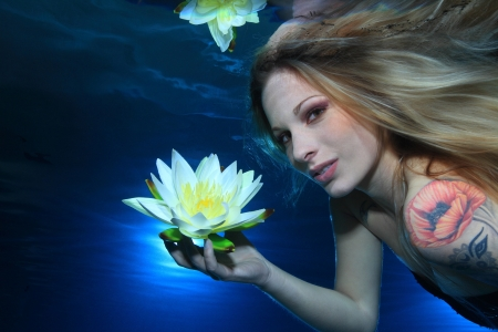 Woman underwater with flower  photo