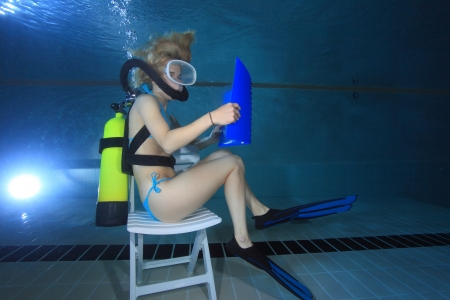 Female diver reading underwater  Banco de Imagens