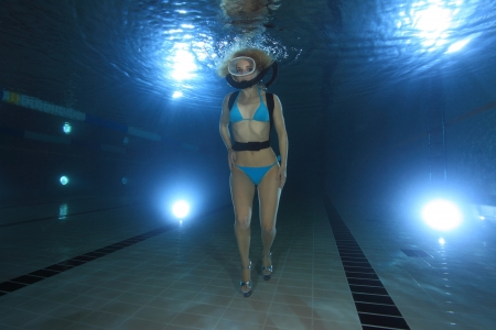 Female diver walking on high heels underwater