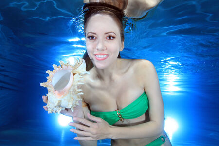 woman underwater with sea shell  Фото со стока