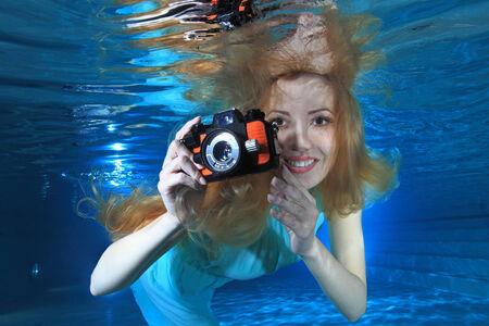 Vrouw onderwater met fotocamera Stockfoto