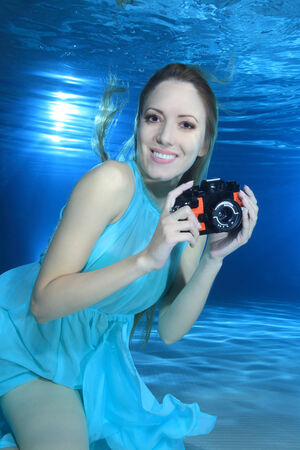 woman diving: Woman underwater with photo camera  Stock Photo