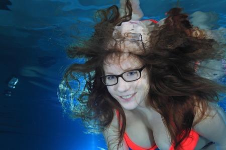 Femme sous-marine dans la piscine avec des lunettes Banque d'images