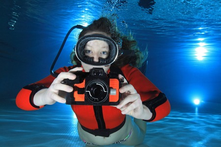 Scuba woman with camera underwater in the pool