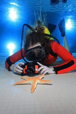 Scuba woman with camera andf starfish   photo