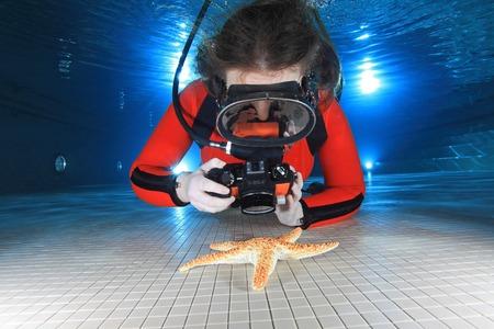 Scuba Frau mit Kamera undf Seestern
