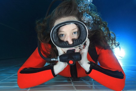 Scuba woman with red neoprene suit in the pool  Stock Photo