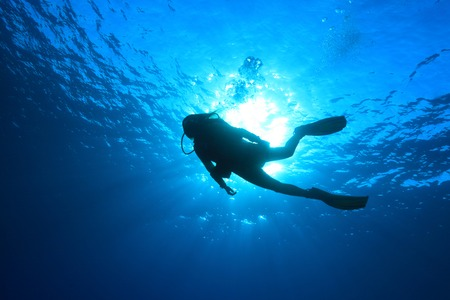Silhouette of scuba diver in the ocean Standard-Bild