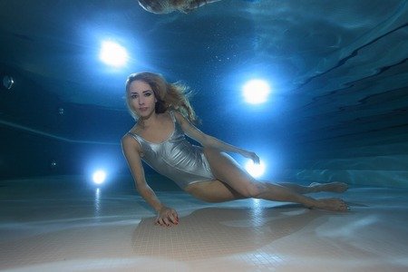 swimming shoes: Underwater model with silver swimsuit in the pool