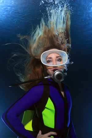 submerge: Scuba woman with long hair underwater