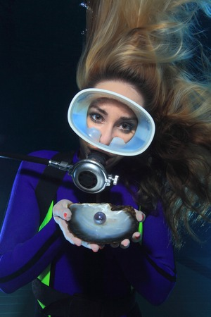 Female scuba diver and shell with pearl photo
