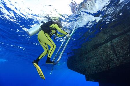 keel: Scuba diver climb the ladder of dive boat