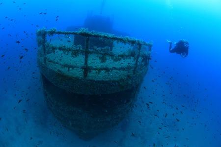 Shipwreck and diver in the mediterranean sea