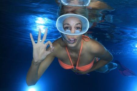 Happy female snorkeler show underwater signal  photo