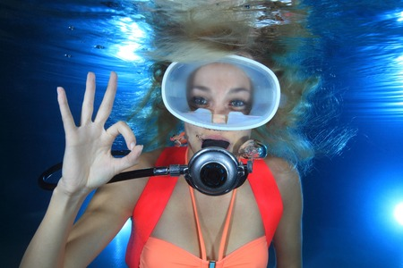 Happy female scuba diver show underwater signal  photo