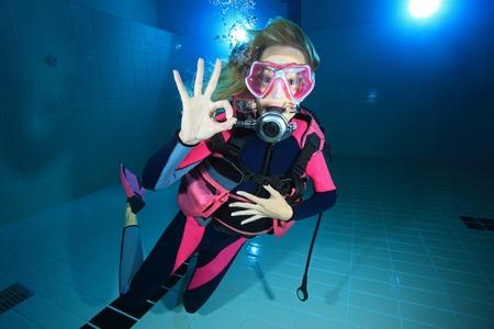 Vrouwelijke duiker onderwater tonen signaal
