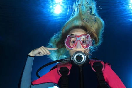 Female scuba diver show signal ear problems  Stock Photo