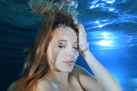 immersion: Young woman underwater