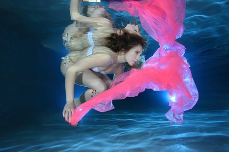 Young woman underwater with pink foulard  photo
