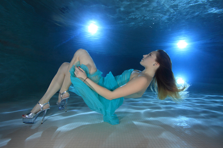 Woman with dress posing underwater