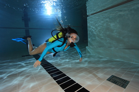 woman diving: Female scuba diver with suit underwater