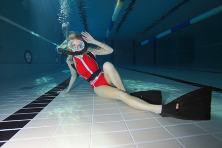 Female scuba diver with red swimsuit diving in the pool