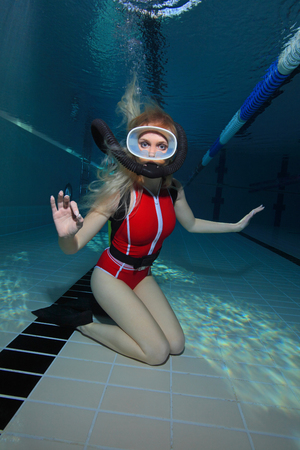 underwater sport: Female scuba diver with red swimsuit diving in the pool