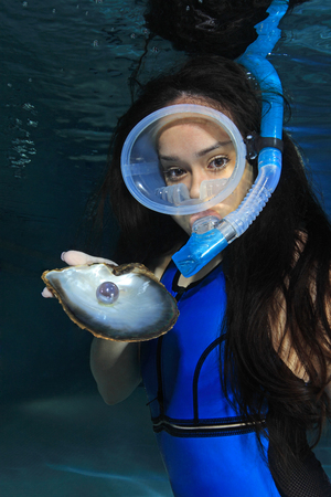 monokini: Female snorkeler with sea shell and pearl