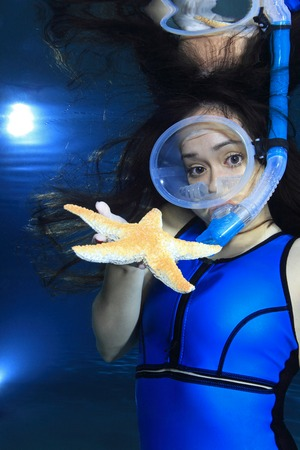 picada: Mujer bajo el agua buceador con estrellas de mar Foto de archivo