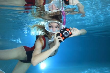Sexy female snorkeler with underwater camera