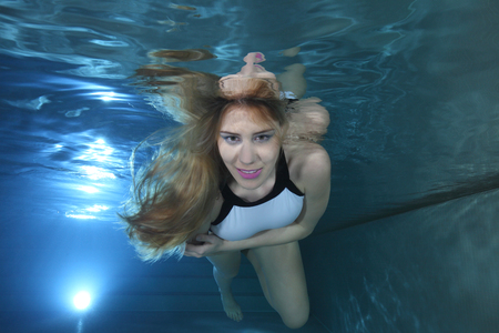 Beautiful woman underwater in the pool Stock Photo