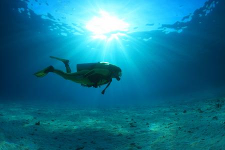 Buzo de buceo y la luz del sol en el océano azul