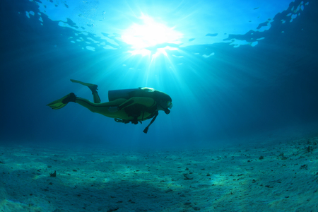 Scuba diver and sunlight in the blue ocean Standard-Bild