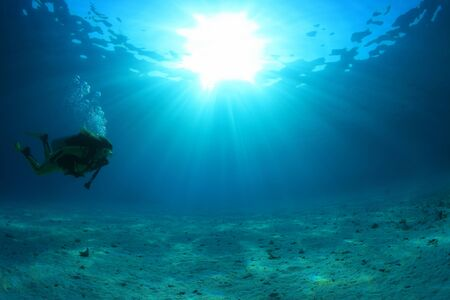 Scuba diver and sunlight in the blue ocean Stock Photo