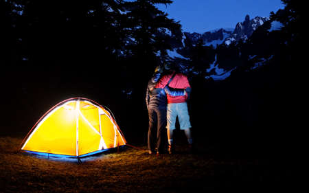 torchlight: Young Couple Hugging at Night Camping in Mountains. Banff National Park, Rocky Mountains, Alberta, Canada.