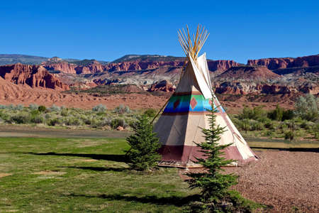 red rocks: Camping at American First Nation Traditional Teepee. Red Rocks at Capitol Reef National Park, Utah, USA. Stock Photo