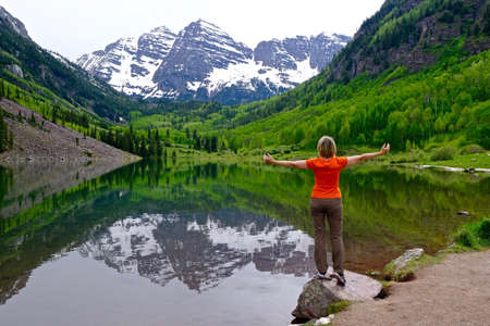 colorado state: Woman Standing by Lake Enjoying Mountain View and Reflection.  Bells near Aspen, Colorado State, USA. Stock Photo
