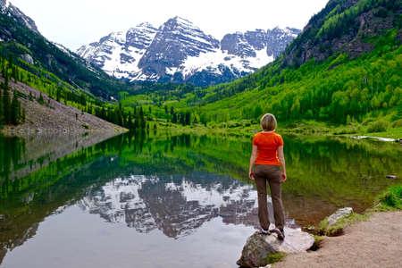 Woman Standing by Lake Enjoying Mountain View and Reflection. Maroon Bells near Aspen, Snowmass,  Colorado State, USA. 免版税图像