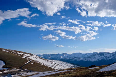 snow fields: Mountain Road through Snow Fields under Sky and Clouds. Trail Ridge Road in Rocky Mountains National park near Estes Park and Denver, Colorado State, USA. Stock Photo