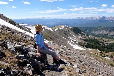 rocky mountains colorado: Woman sitting on rocks enjoying mountain view. Cottonwood Pass near Buena Vista and Denver  in Rocky Mountains, Colorado, USA. Stock Photo