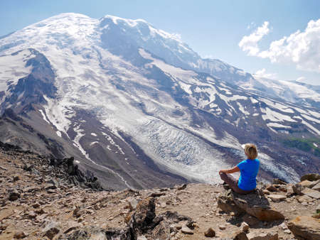 snow capped mountain: Woman in yoga pose sitting by snow capped mountain. Burroughs Mountain Trail, Mount Rainier National Park, Seattle, Washington, USA.