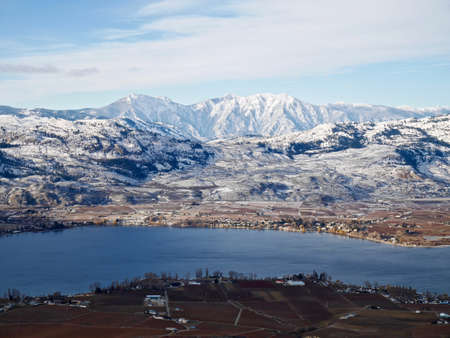 snow capped mountains: Little village by lake surrounded by snow capped mountains. Winter in Osoyoos, Ocanagan Valley, British Columbia, Canada. Stock Photo