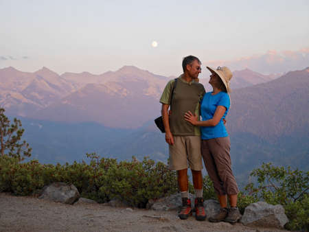 sequoia national park: Happy couple smiling and hugging. Moonlit Sierra Nevada mountains. Eagle View in Sequoia National Park, Visalia,  California, USA.