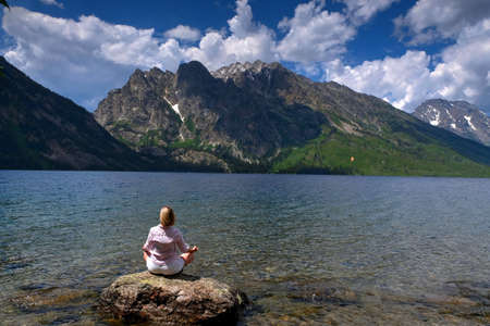 Woman in yoga pose by Jenny Lake in Grand Tetons National Park, Jackson, Wyoming.