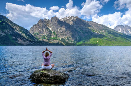 jenny: Woman in yoga pose by lake and mountains. Jenny Lake in Grand Tetons National Park, Jackson, Wyoming.