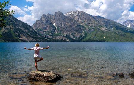 jenny: Woman meditating by lake and mountains. Jenny Lake in Grand Tetons National Park, Jackson, Wyoming. Stock Photo