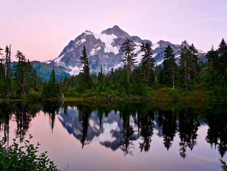 Ski Area: Reflection of mountain in calm water at sunset. Picture Lake and Mount Shuksan  at Mount Baker Ski Area. Cascade Mountains near Bellingham, Washington, USA. Stock Photo